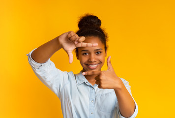 Happy african teenage girl making frame of fingers