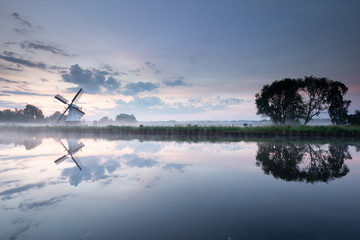 Wall Mural - white windmill by river with sky reflection