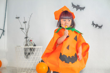 little girl with pumpkin is celebrating Halloween party Wall mural