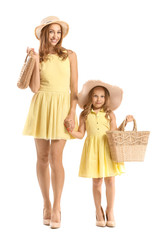 Portrait of fashionable woman with her little daughter on white background