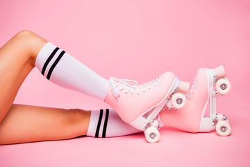 Cropped photo of girls foot wearing four -wheeled equipment quads lying isolated over pink...