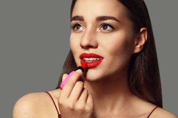 Beautiful young woman with bright lipstick on grey background Wall mural
