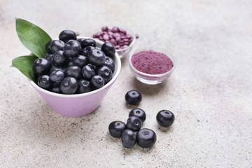 Acai berries with powder and tablets on light background