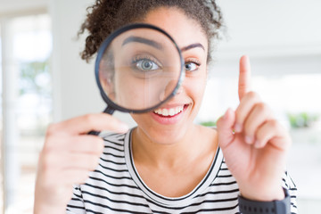 Young african american woman looking through magnifying glass surprised with an idea or question pointing finger with happy face, number one Fotomurales