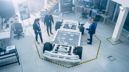 Team of Automobile Design Engineers in Automotive Innovation Facility. They are Working on Electric Car Platform Chassis Prototype that Includes Wheels, Suspension, Hybrid Engine and Battery.