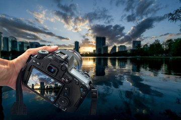A DSLR camera held by one hand in the frame aiming towards beautiful sunset, blue skies, and white clouds behind a city scape. The digital display showing the picture that will be taken.