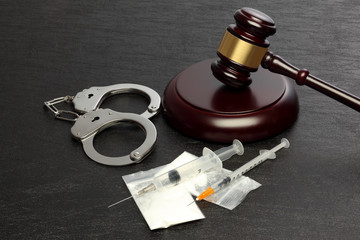 Police handcuffs and syringe with drug