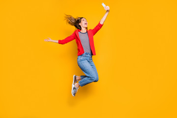 Full size photo of lovely girl jumping making photos laughing isolated over yellow background
