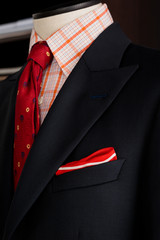 Detail of dark grey man suit with red tie