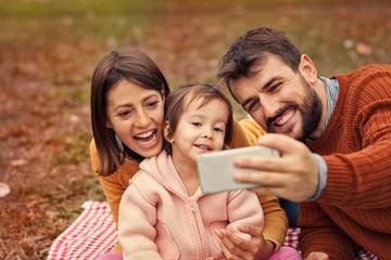 Happy family taking selfie, posing for photo.