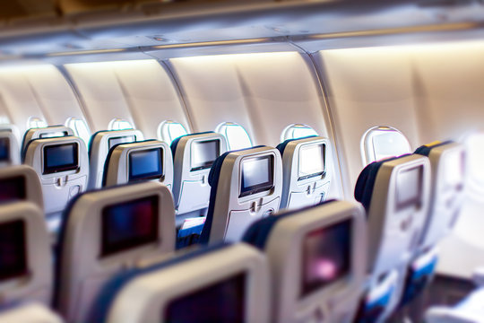 Modern aircraft interior with seats and blank touch entertainment screens displays. Concept of fast and comfort travel and new technologies.