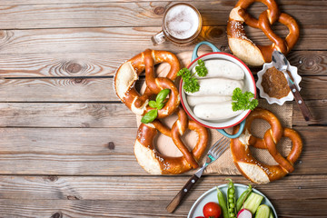 Pretzels, white bavarian sausages and vegetables on wooden background, german traditional food, oktoberfest Wall mural