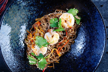 Close up on buckwheat noodles with shrimps served in black textured bowl. Thai cuisine. Seafood. Reaydy for eat. Picture for recipe. Copy space for design. Soba seafood. Top view