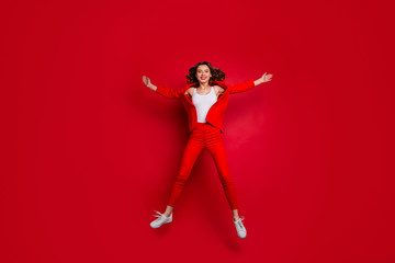 Full length photo of lovely girl with bright lips stick raising hands jumping isolated over red background
