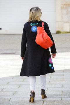 Paris, France - March 27, 2017: Back view of a well dressed blond woman walking on the city streets