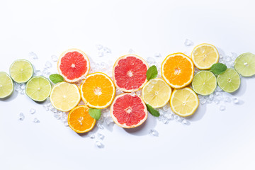 Colorful fruits backround. .citrus slices,orange, lemon, lime, and grapefruit with ice and mint. white background. Top view