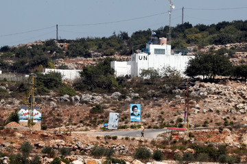 A banner depicting Hezbollah leader Sayyed Hassan Nasrallah and an United Nation's post are seen in Lebanon from the Israeli side of the border, near Zar'it in northern Israel