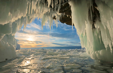 Unusual winter landscape of the frozen Baikal Lake. Beautiful view on sunset from an ice grotto with many icicles in the rocks of Olkhon Island. Winter tourism. Natural cold background