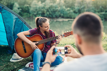woman playing guitar while her boyfriend taking picture of her. camping by the lake