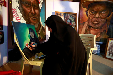 An Iraqi woman paints at a photo gallery in the holy shiite city of Najaf