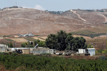 Israeli military vehicles are seen in the foreground as Lebanon is seen in the background in this general view picture taken from the Israeli side of the border, near Zar'it in northern Israel