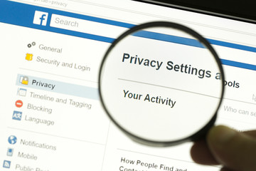 """Hand holding a magnifying glass and magnifying the word """"Privacy settings"""""""