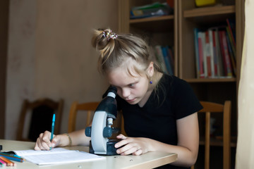 Girl 12 years old doing homework in chemistry with   microscope.