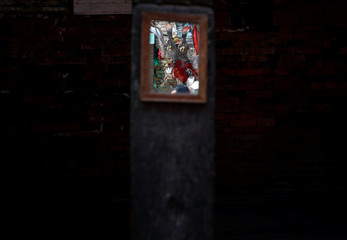 A devotee, cloaked inside the statue of Buddha, is seen in the mirror as the parade passes by, during the Pancha Dan festival, in Bhaktapur