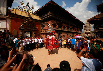 A devotee, cloaked inside the statue of Buddha, parades during the Pancha Dan festival in Bhaktapur