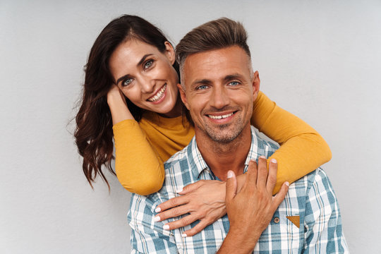 Cheerful optimistic adult loving couple isolated over grey wall background.