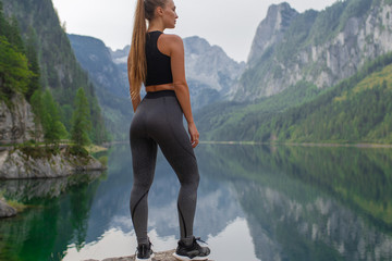 In de dag Ontspanning Young sexy athletic girl in the mountains near the lake