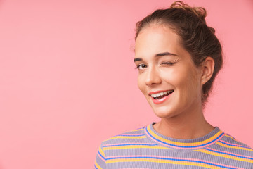 Image closeup of happy beautiful woman dressed in colorful clothes smiling and winking at camera