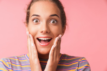 Image closeup of amazed young woman dressed in colorful clothes smiling and touching her cheeks