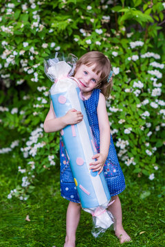 4 years old girl hugs big candy. Summertime in the garden.