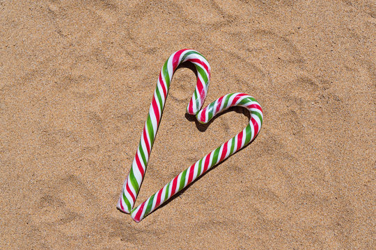 Christmas candy cane heart on sandy beach with copy space.