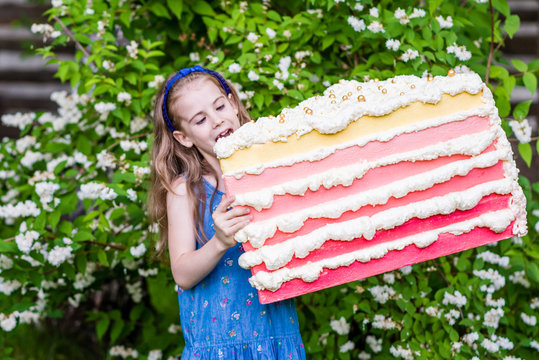 8 years old girl try to bite the piece of cake. Summer party outdoor.