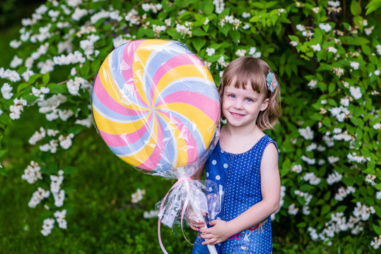 4 years old girl holds big lollypop. Summertime in the garden.