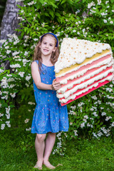8 years old girl hold the piece of cake. Summer party outdoor.