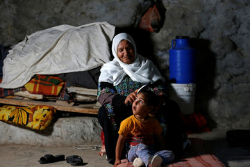 Palestinian woman combs the hair of her granddaughter inside a cave they live in, near Yatta in the Israeli-occupied West Bank
