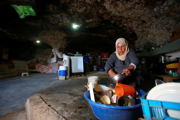 Palestinian woman washes kitchen utensils inside a cave she lives in, near Yatta in the Israeli-occupied West Bank