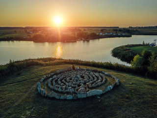 Spiral labyrinth made of stones, on sunset lake