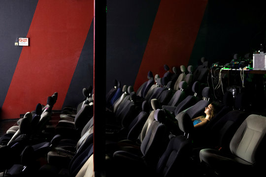 """A woman watches a screening in a deserted cinema hall fitted with old car seats at a venue showcasing various artworks and art performances pieces as part of a recent project by Jerusalem's art collective, """"Taltalistim"""" in an industrial area in Jerusalem"""