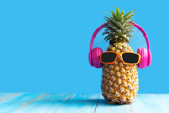 Summer in the party.  Hipster Pineapple Fashion in sunglass and music bright beautiful color in holiday, Creative art fruit for tropical style on the beach vibes, blue background.  Fashion Summer