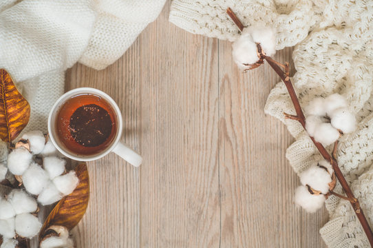 Background with warm sweaters and cup tea. Cozy still life in warm shades, space for text
