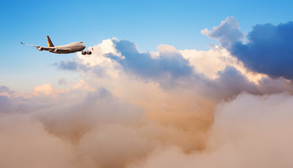 Huge commercial airplane above clouds
