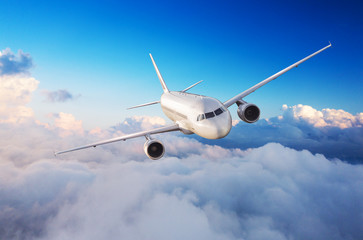 Passengers commercial airplane flying above clouds Fotobehang