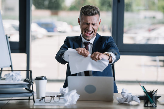 selective focus of irritated man screaming while tearing paper near disposable cup