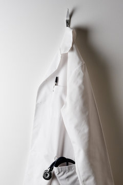 A Doctors White Lab Coat and Hanging on a Hook with Stethoscope in pocket.