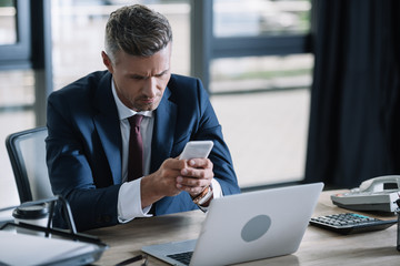handsome businessman using smartphone near laptop and document tray