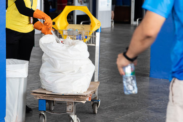 Cleaning staff separating plastic bottles from trash